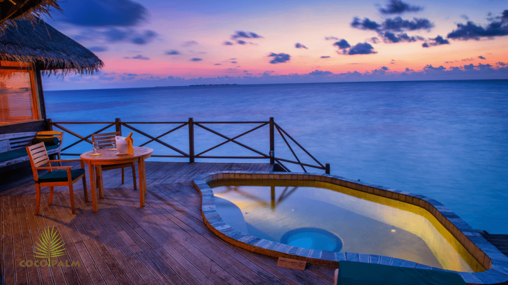 A sunset picture in the ocean. Shows a cabana and hottub during sunset