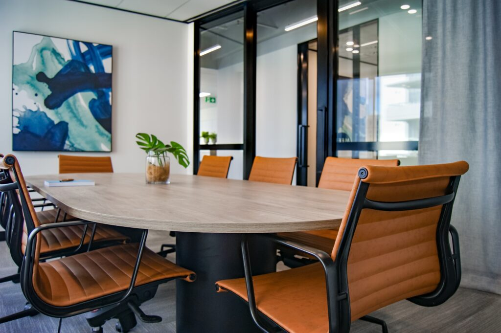 A modern conference room with an oval table and tan leather chairs.