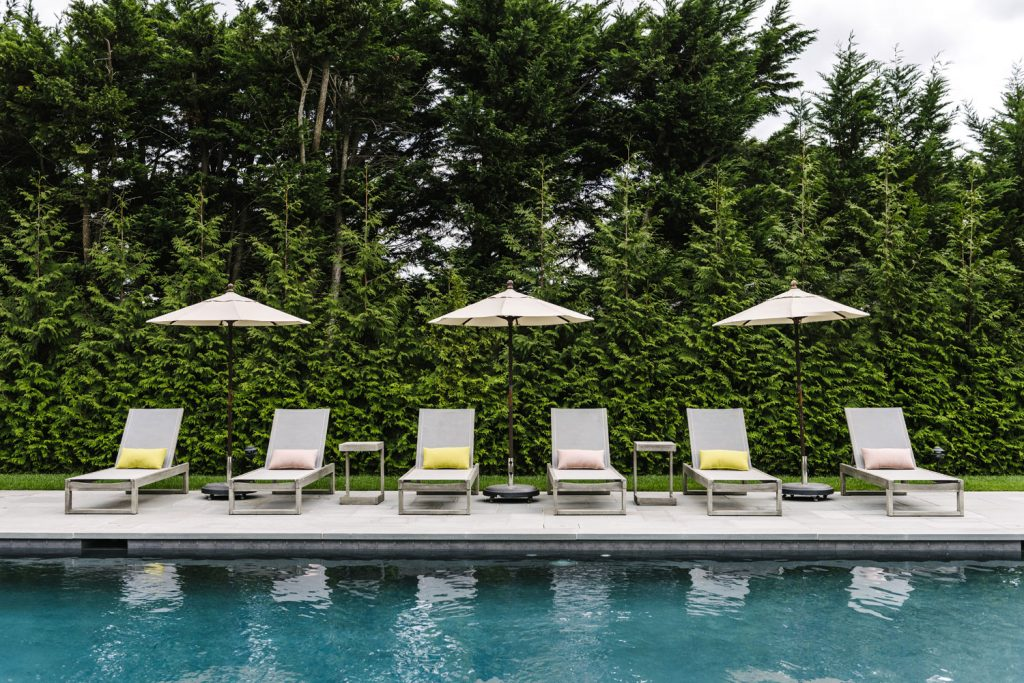 A photo of pool chairs and a pool surrounded by pines.