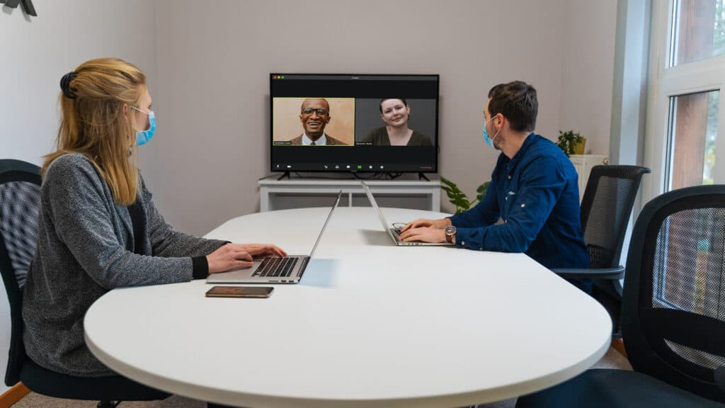 Two masked individuals are video conferencing with two colleagues via Zoom in a conference room.