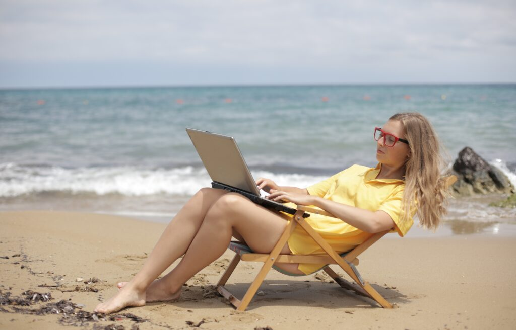 Woman working on a laptop at the beach.