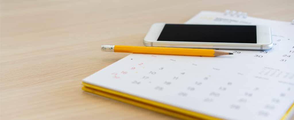 An agenda, pencil and phone.